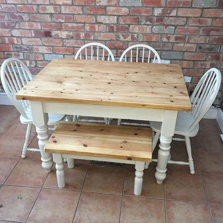 Square dining table made from reclaimed wood with 4 chairs and small bench